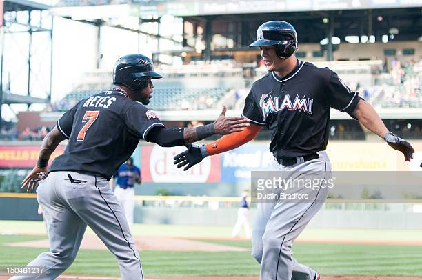 Giancarlo Stanton and Jose Reyes of the Miami Marlins celebrate after Stanton hit a threerun home run in the first inning of a game against the...
