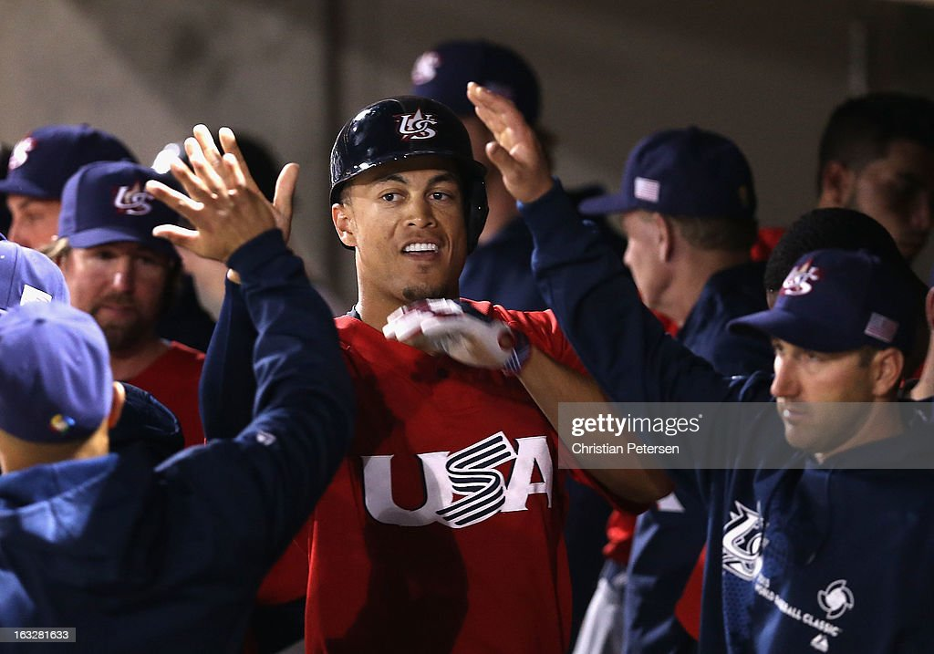 <a gi-track='captionPersonalityLinkClicked' href=/galleries/search?phrase=Giancarlo+Stanton&family=editorial&specificpeople=8983978 ng-click='$event.stopPropagation()'>Giancarlo Stanton</a> #27 of Team USA high fives teammates in the dugout after scoring against the Colorado Rockies during the spring training game at Salt River Fields at Talking Stick on March 6, 2013 in Scottsdale, Arizona.