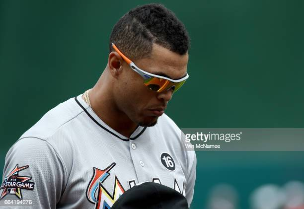 Giancarlo Stanton of the Miami Marlins bows his head during the playing of the national anthem at the Opening Day game against the Washington...