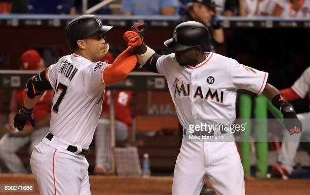 Giancarlo Stanton of the Miami Marlins celebrates a two run home run in the third inning with Dee Gordon during a game against the Philadelphia...