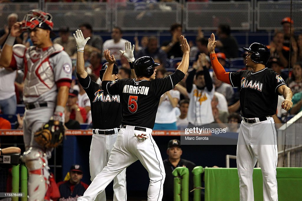 Giancarlo Stanton #27 (R) of the Miami Marlins celebrates against the Washington Nationals with teammates Logan Morrison #5 and Justin Ruggiano #20 during the first inning at Marlins Park on July 12, 2013 in Miami, Florida. The Marlins defeated the Nationals 8-3.