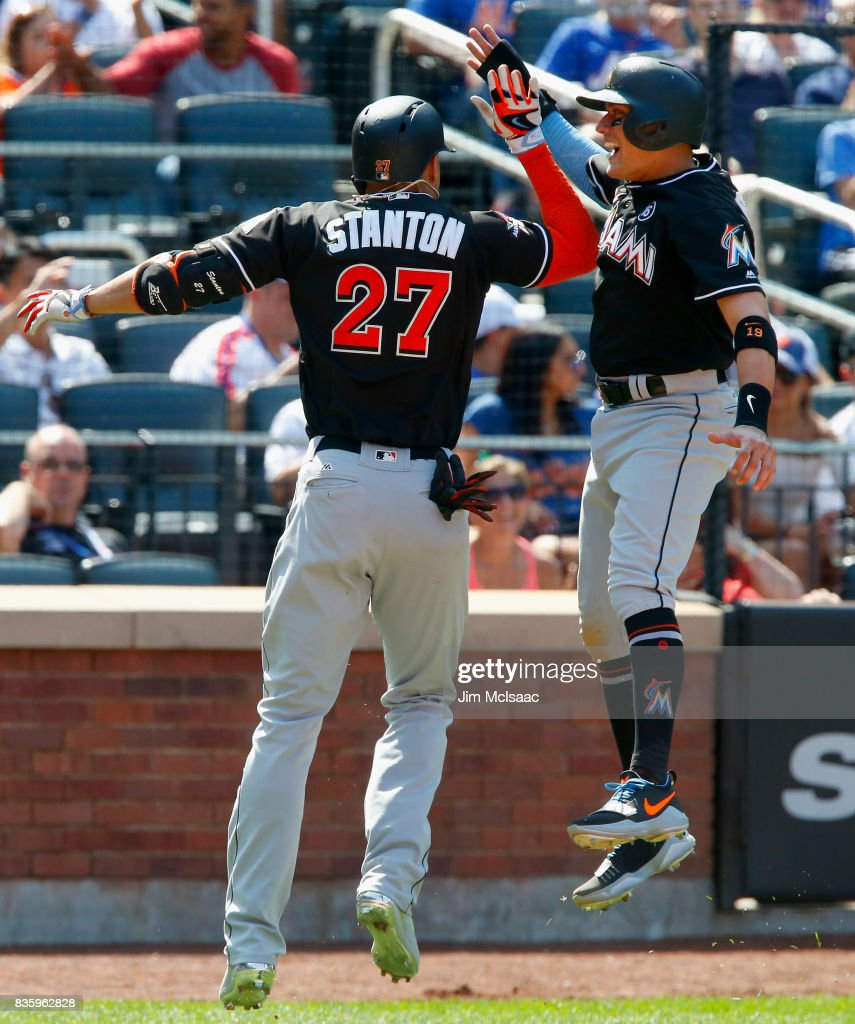 Giancarlo Stanton #27 of the Miami Marlins celebrates his seventh inning three run home run against the New York Mets with teammate Miguel Rojas #19 at Citi Field on August 20, 2017 in the Flushing neighborhood of the Queens borough of New York City.