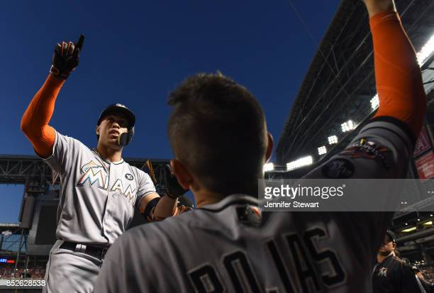 Giancarlo Stanton of the Miami Marlins celebrates in the dugout after hitting a solo home run in the fourth inning against the Arizona Diamondbacks...