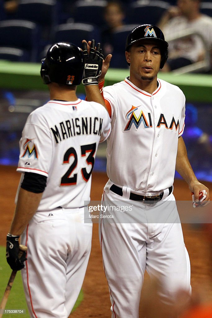 <a gi-track='captionPersonalityLinkClicked' href=/galleries/search?phrase=Giancarlo+Stanton&family=editorial&specificpeople=8983978 ng-click='$event.stopPropagation()'>Giancarlo Stanton</a> #27 (R) of the Miami Marlins celebrates scoring a run with teammate Jake Marisnick #23 against the Cleveland Indians at Marlins Park on August 2, 2013 in Miami, Florida.