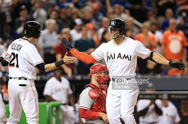 Giancarlo Stanton of the Miami Marlins celebrates with Christian Yelich after hitting a two run home run during the eighth inning of the game against...