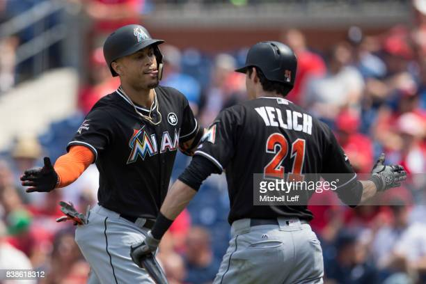 Giancarlo Stanton of the Miami Marlins celebrates with Christian Yelich after hitting a solo home run in the top of the third inning at Citizens Bank...