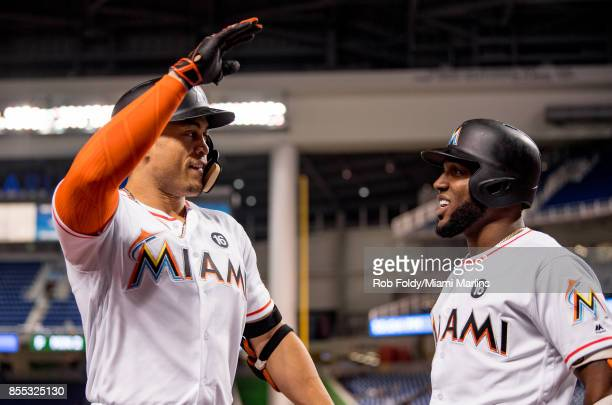 Giancarlo Stanton of the Miami Marlins celebrates with Marcell Ozuna after hitting his fiftyninth home run of the season during the eighth inning of...