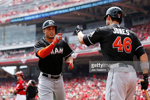 Giancarlo Stanton of the Miami Marlins celebrates with teammate Garrett Jones after hitting a home run in the first inning of the game against the...