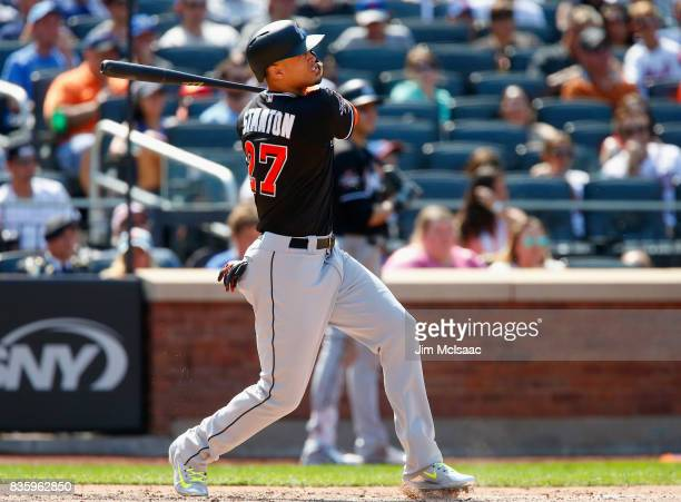 Giancarlo Stanton of the Miami Marlins follows through on a seventh inning three run home run against the New York Mets at Citi Field on August 20...