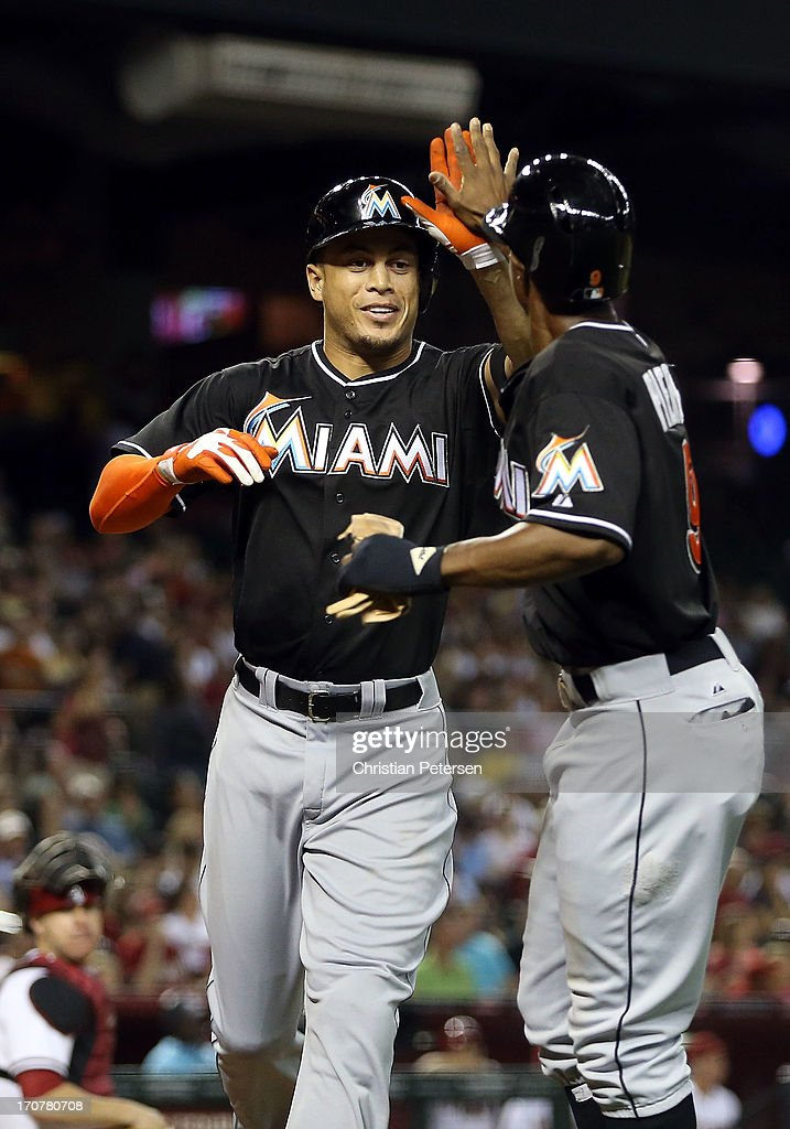 <a gi-track='captionPersonalityLinkClicked' href=/galleries/search?phrase=Giancarlo+Stanton&family=editorial&specificpeople=8983978 ng-click='$event.stopPropagation()'>Giancarlo Stanton</a> #27 of the Miami Marlins high-fives <a gi-track='captionPersonalityLinkClicked' href=/galleries/search?phrase=Juan+Pierre&family=editorial&specificpeople=202961 ng-click='$event.stopPropagation()'>Juan Pierre</a> #9 after Stanton hit a two-run home run against the Arizona Diamondbacks during the sixth inning of the MLB game at Chase Field on June 17, 2013 in Phoenix, Arizona.