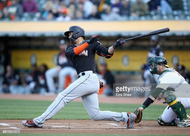 Giancarlo Stanton of the Miami Marlins hits a single that scored Dee Gordon in the first inning against the Oakland Athletics at Oakland Alameda...