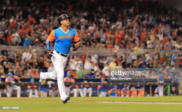 Giancarlo Stanton of the Miami Marlins hits a solo home run in the third inning during a game against the San Diego Padres at Marlins Park on August...