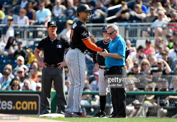 Giancarlo Stanton of the Miami Marlins is checked out by trainer Mike Kozak after being hit by a pitch in the first inning during the game against...
