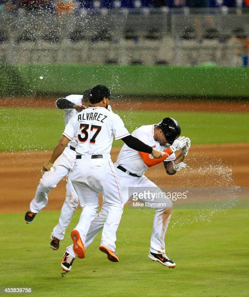 Giancarlo Stanton of the Miami Marlins is congratulated after hitting a walk off single to beat the Texas Rangers 43 at Marlins Park on August 19...
