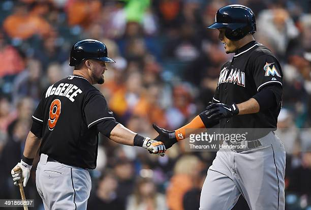 Giancarlo Stanton of the Miami Marlins is congratulated by Casey McGehee after Stanton hit a solo home run against the San Francisco Giants in the...