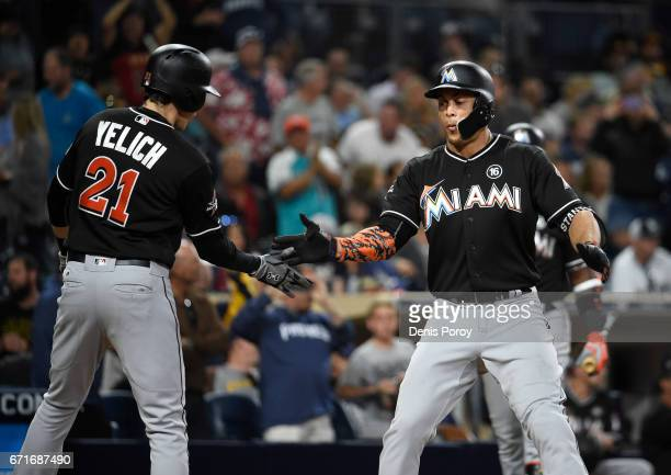Giancarlo Stanton of the Miami Marlins is congratulated by Christian Yelich after hitting a tworun home run during the eleventh inning of a baseball...