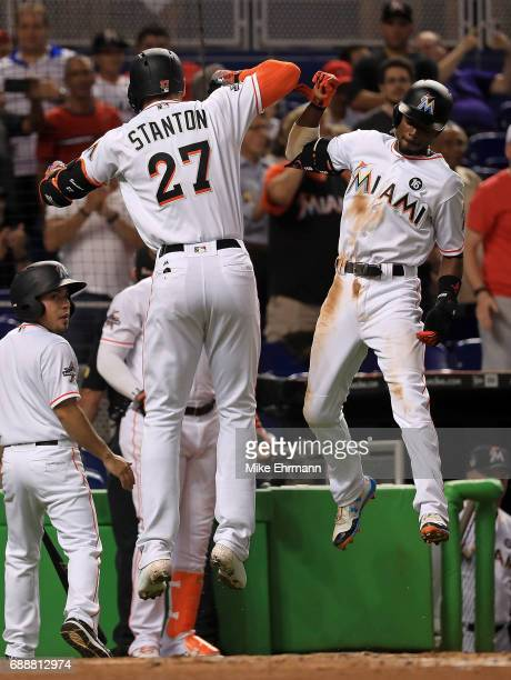 Giancarlo Stanton of the Miami Marlins is congratulated by Dee Gordon after hitting a two run home run in the first inning during a game against the...