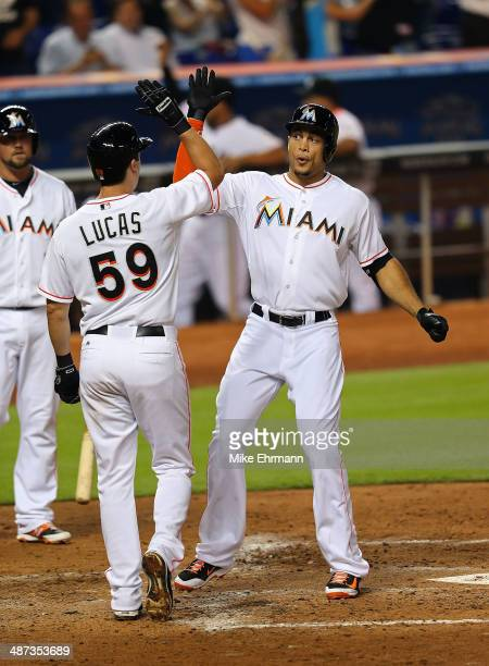 Giancarlo Stanton of the Miami Marlins is congratulated by Ed Lucas after hitting a two run home run during a game against the Atlanta Braves at...