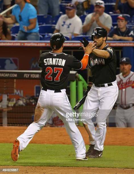 Giancarlo Stanton of the Miami Marlins is congratulated by Garrett Jones after scoring during a game against the Atlanta Braves at Marlins Park on...