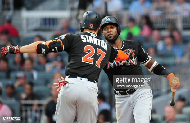 Giancarlo Stanton of the Miami Marlins is congratulated by Marcel Ozuna after hitting a sixth inning solo home run against the Atlanta Braves at...