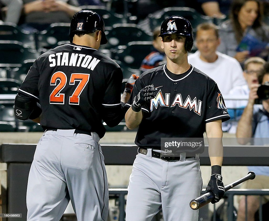Giancarlo Stanton #27 of the Miami Marlins is congratulated by teammate Ed Lucas #59 of the Miami Marlins after Stanton hit a solo home run in the second inning against the New York Mets on August 13, 2013 at Citi Field in the Flushing neighborhood of the Queens borough of New York City.