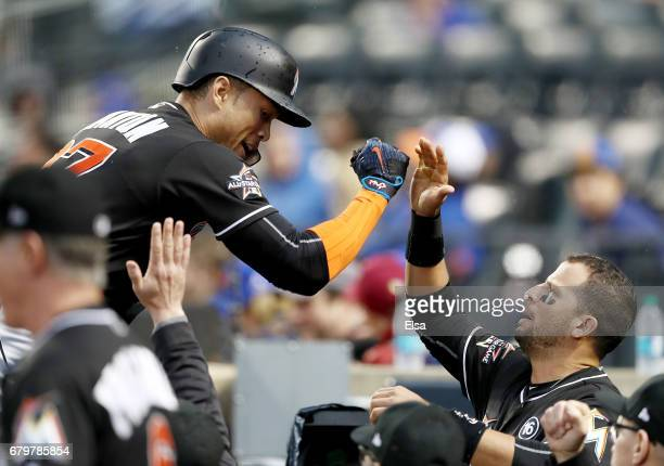 Giancarlo Stanton of the Miami Marlins is congratulated by teammate Martin Prado after Stanton hit a solo home run in the second inning against the...