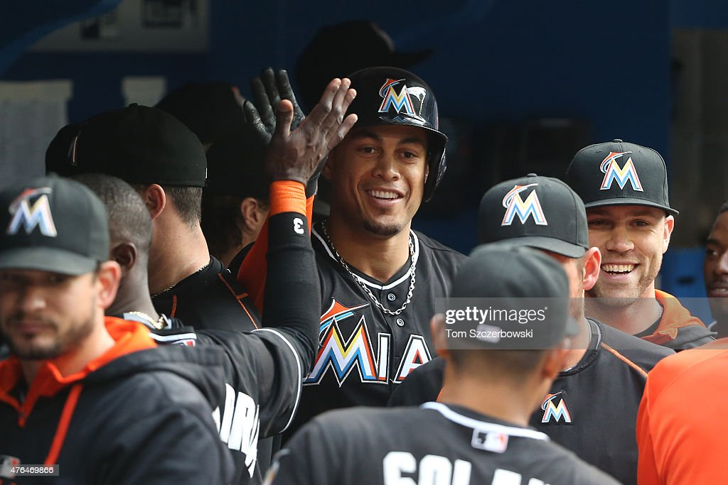 Giancarlo Stanton of the Miami Marlins is congratulated by teammates in the dugout after hitting a solo home run in the first inning during MLB game...