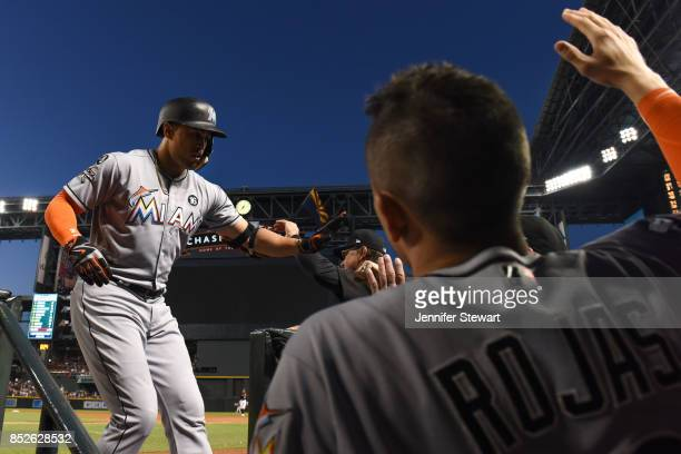 Giancarlo Stanton of the Miami Marlins is congratulated in the dugout after hitting a solo home run in the fourth inning against the Arizona...