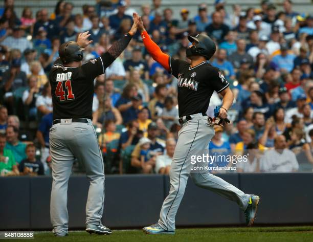 Giancarlo Stanton of the Miami Marlins is greeted by Justin Bour as he scores during the first inning of their game against the Milwaukee Brewers at...