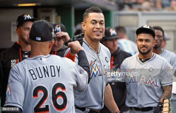 Giancarlo Stanton of the Miami Marlins is greeted by teammates in the dugout after hitting a solo home run in the third inning during the game...