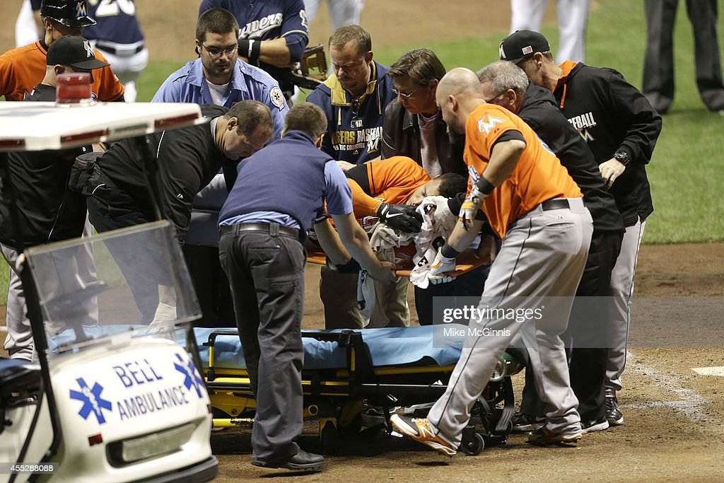 Giancarlo Stanton of the Miami Marlins is lifted onto a stretcher after getting hit by a pitch from Mike Fiers of the Milwaukee Brewers during the...
