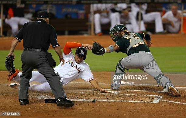 Giancarlo Stanton of the Miami Marlins is tagged out at home by Derek Norris of the Oakland Athletics during a game at Marlins Park on June 27 2014...