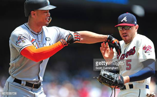 Giancarlo Stanton of the Miami Marlins jokes around during the first inning with Freddie Freeman of the Atlanta Braves at SunTrust Park on August 6...
