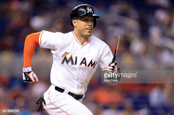 Giancarlo Stanton of the Miami Marlins runs to first base with a broken bat during the fourth inning of the game against the Colorado Rockies at...