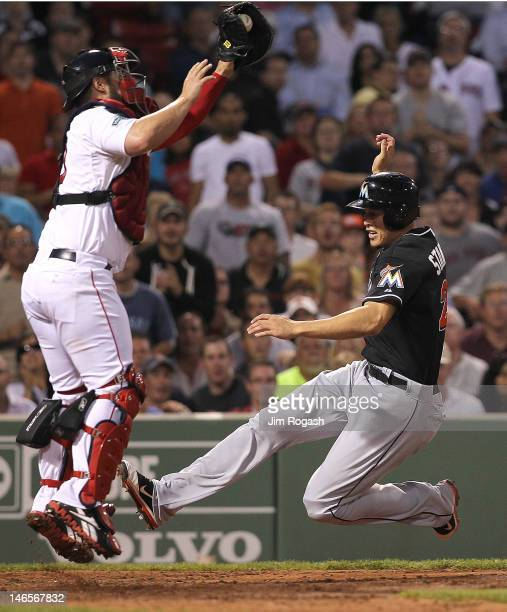 Giancarlo Stanton of the Miami Marlins scores as Kelly Shoppach of the Boston Red Sox fields a late throw in the fifth inning during interleague play...