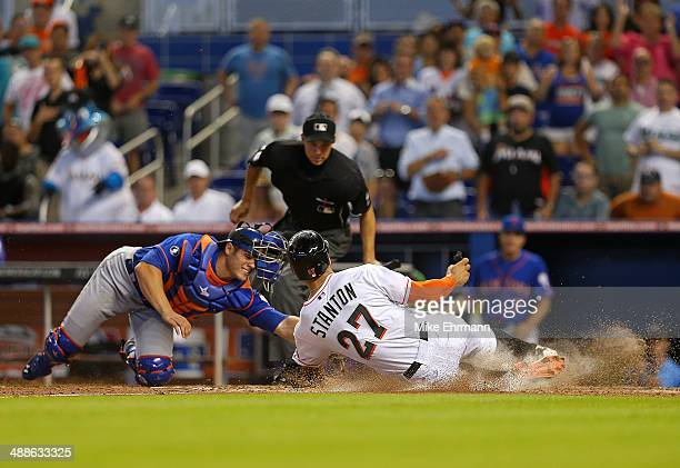 Giancarlo Stanton of the Miami Marlins slides past the tag from Anthony Recker of the New York Mets to score the winning run on a sac fly by Marcell...