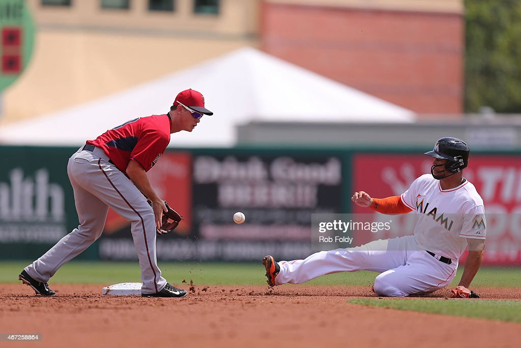Giancarlo Stanton of the Miami Marlins slides safely into second base ahead of the tag from James Beresford of the Minnesota Twins during the first...