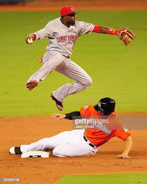 Giancarlo Stanton of the Miami Marlins slides under Brandon Phillips of the Cincinnati Reds for an out at Marlins Park on September 16 2012 in Miami...