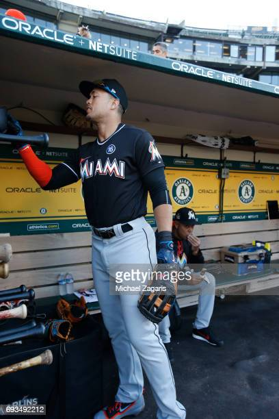 Giancarlo Stanton of the Miami Marlins stands in the dugout prior to the game against the Oakland Athletics at the Oakland Alameda Coliseum on May 23...