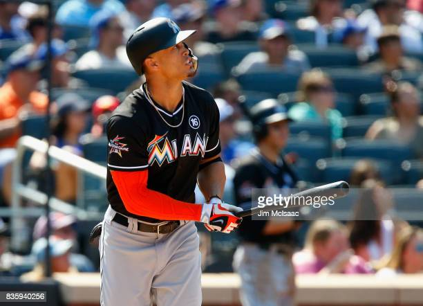 Giancarlo Stanton of the Miami Marlins watches the flight of his seventh inning three run home run against the New York Mets at Citi Field on August...