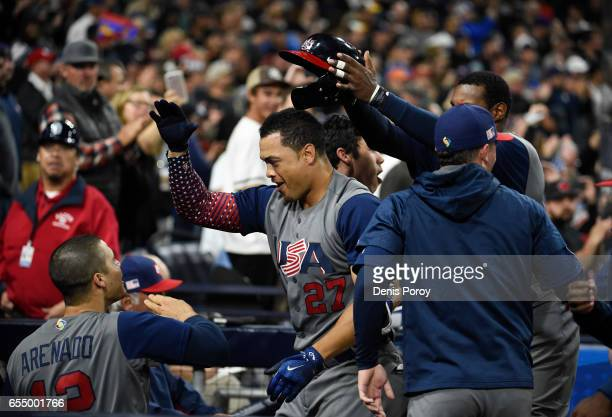 Giancarlo Stanton of the United States center is congratulated in the dugout by after hitting a two run home run during the fourth inning of the...