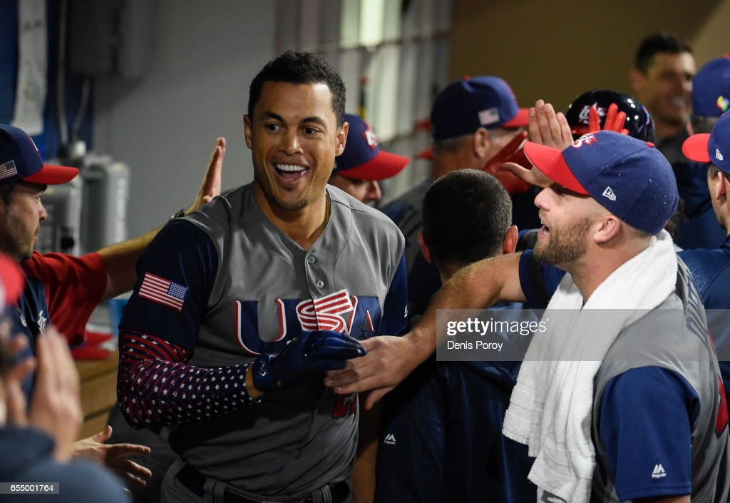 Giancarlo Stanton #27 of the United States, left, is congratulated in the dugout by after hitting a two run home run during the fourth inning of the World Baseball Classic Pool F Game Six between the United States and the Dominican Republic at PETCO Park on March 18, 2017 in San Diego, California.