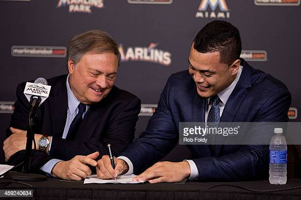 Giancarlo Stanton signs a contract with the Miami Marlins as owner Jeffrey Loria looks on during a press conference at Marlins Park on November 19...