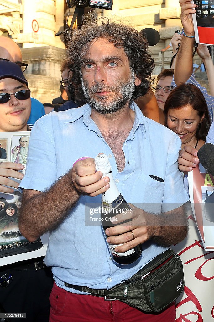 Gianfranco Mascia of 'Popolo Viola' movement opens a bottle of champagne as he reacts in front of the Justice palace to the verdict of the 'Corte di Cassazione' (Supreme Court) during the final session to judge former Italian Prime Minister Silvio Berlusconi on August 1, 2013 in Rome, Italy. The judges of the supreme court rejected Berlusconi's final appeal against the conviction for tax fraud, sentencing him to four years in prison.