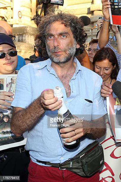 Gianfranco Mascia of 'Popolo Viola' movement opens a bottle of champagne as he reacts in front of the Justice palace to the verdict of the 'Corte di...