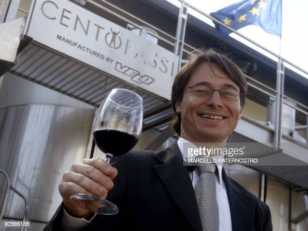 Gianluca Faraone chairman of Cooperativa Centopassi poses with a glass of red wine in front of the factory in San Cipirello on October 27 2009 during...