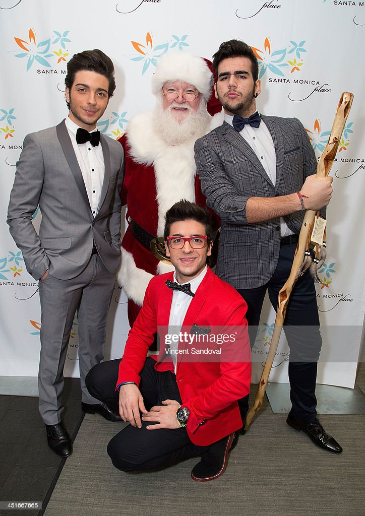 Gianluca Ginoble Ignazio Boschetto and Piero Barone of Il Volo pose with Santa Claus during the HGTV Holiday House KickOff at Santa Monica Place with...