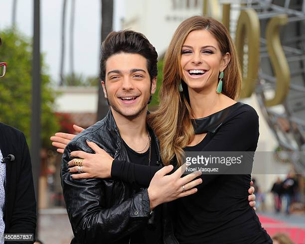 Gianluca Ginoble of Il Volo and Maria Menounos visit 'Extra' at Universal Studios Hollywood on November 20 2013 in Los Angeles California