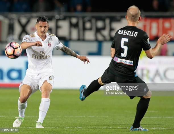 Gianluca Lapadula of AC Milan is challenged by Andrea Masiello of Atalanta BC during the Serie A match between Atalanta BC and AC Milan at Stadio...