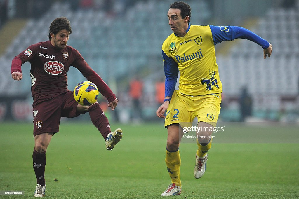 Gianluca Sansone (L) of Torino FC in action against Dario Dainelli of AC Chievo Verona during the Serie A match between Torino FC and AC Chievo Verona at Stadio Olimpico di Torino on December 22, 2012 in Turin, Italy.